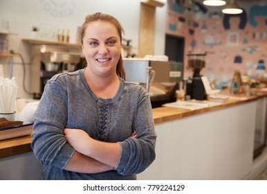 Young woman smiling to camera at the counter in a bakery