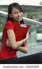 Young woman smiling at camera, hugging folder