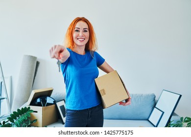 Young woman smiling at camera while holding cardboard box and keys to new apartment