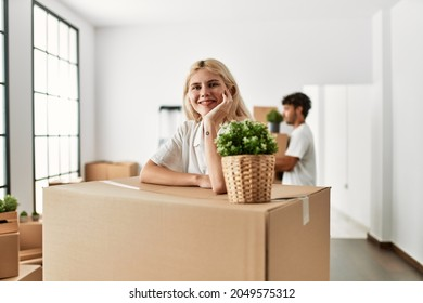 Young woman smiling happy leaning on cardboard at new home.