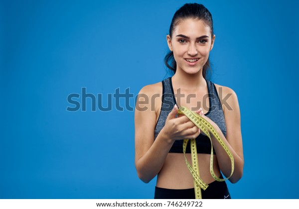 young woman smiling in her hand measuring tape on blue background, sport, fitness