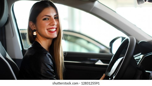 Young woman smiling in her new car in a showroom