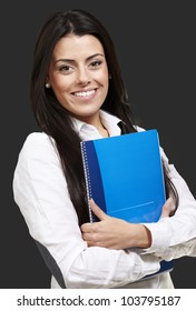 young woman smiling and holding a notebook against a black background