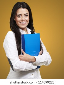young woman smiling and holding a notebook against an orange background