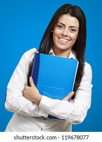 young woman smiling and holding a notebook against a blue background