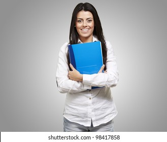 young woman smiling and holding a notebook against a grey background