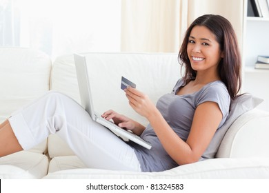 young woman smiling into camera with credit card in hands in living room