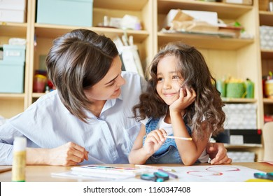 Young woman smiling and looking at cheerful girl while painting together during lesson in art school