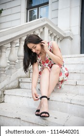 young woman smiling and looking at her shoes