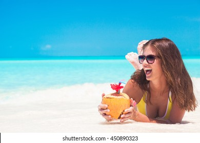 young woman smiling lying in bikini and sunglasses with coconut on beach