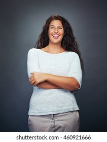 Young Woman Smiling On Grey Background Looking Into Camera