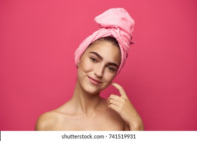 young woman smiling on a pink background