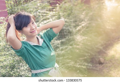 Young woman smiling outdoors portrait. Soft sunny colors.