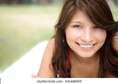 Young woman smiling in a park and looking at the camera.