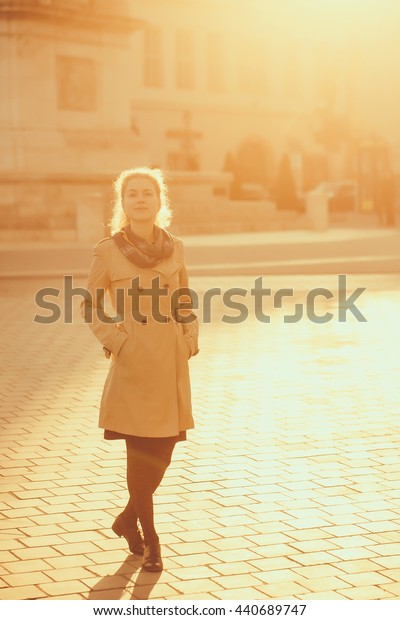Young woman with smiling pretty face and curly hairstyle in fashionable beige autumn coat standing outdoor in street in sun light