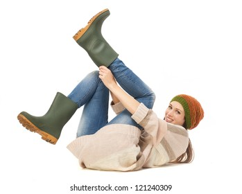 Young woman smiling and putting on gardening boots. Isolated on white background