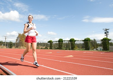 Young  woman smiling and running at a track. Horizontally framed photo.