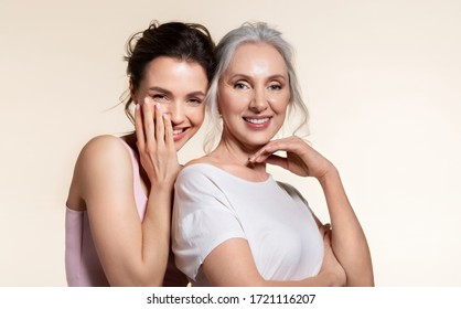 Young woman and smiling senior lady hugging portrait. Modest shy millennial daughter covering face with palm cuddling confident experienced aged mother from back. Trust protection, love support