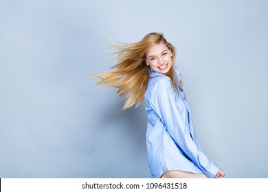 Young woman smiling, in shirt, hair in the wind, looking towards the lens