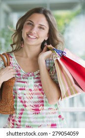 Young woman smiling with shopping bags