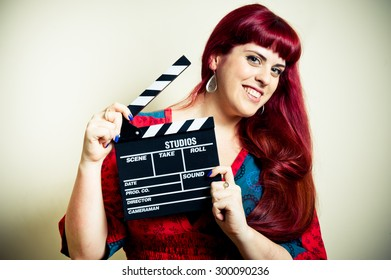 Young woman smiling showing movie clapper board on white background