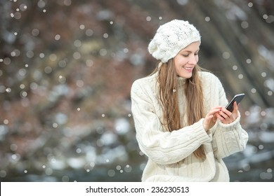 Young  woman smiling with smart phone and winter landscape and snowflakes on the background