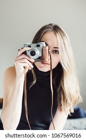 Young woman smiling and taking a photo with a vintage camera looking into the camera.