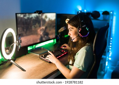 Young woman smiling and talking during a live stream on a smartphone with a ring light. Happy female gamer playing a video game in her computer with neon led lights
