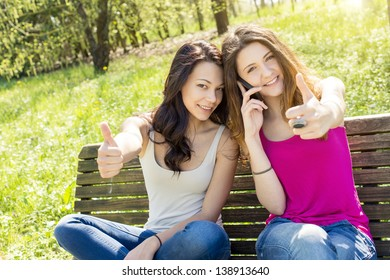 Young woman smiling with thumbs up at the park
