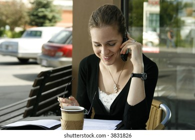 Young woman smiling while doing paperwork and talking on cell phone at cafe.