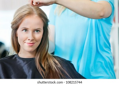 Young woman smiling while hairdresser getting her ready for haircut at parlor