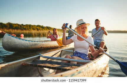 Young woman smiling while paddling a canoe on a scenic lake with a group of friends on a sunny summer afternoon