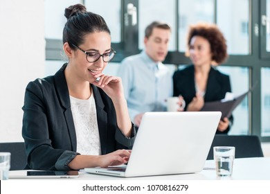 Young woman smiling while using a laptop at desk in the office in front of her colleagues
