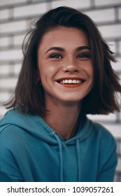 Young woman is smilling. Her teeth ideal and white. Brunette has haircut. She dressed blue hoodie.