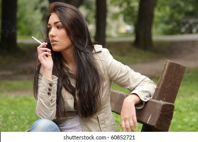 Young woman smoke in park
