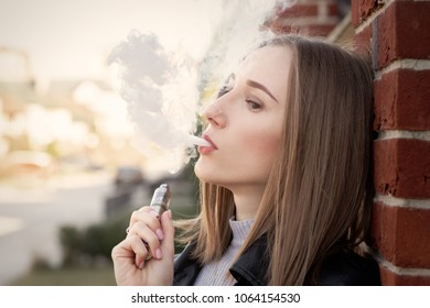 young woman smoking electronic cigarette in the city