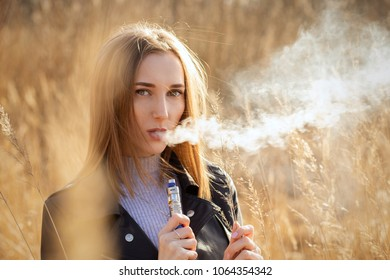 young woman smoking electronic cigarette in the nature