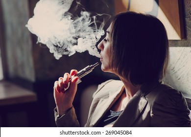 young woman smoking electronic cigarette