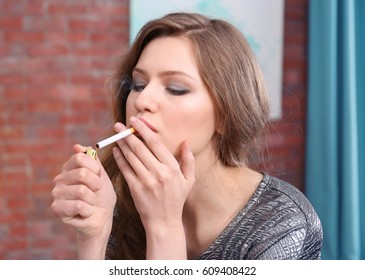Young woman smoking in living room