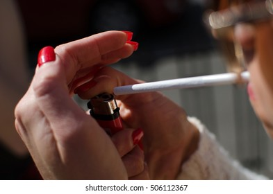 Young woman is smoking on the street