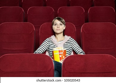 Young woman with a snack food waiting for a friend at the cinema
