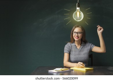 Young woman snapping fingers on board and light bulb over his head