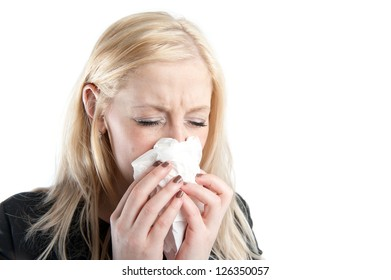 Young woman sneezing into a tissue