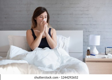 Young woman sneezing nose covered by warm duvet