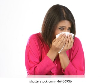 young woman sneezing to a paper handkerchief