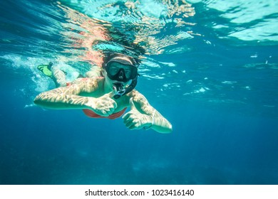 Young woman snorkel, holding two thumbs up, Similan Islands (Phang Nga), Thailand, one of the best snorkeling locations in Andaman sea.