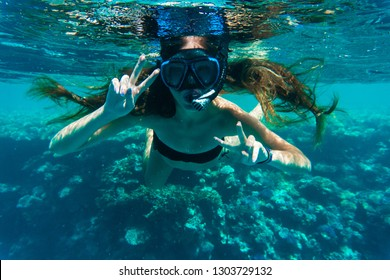 Young woman snorkeling making peace signs underwater