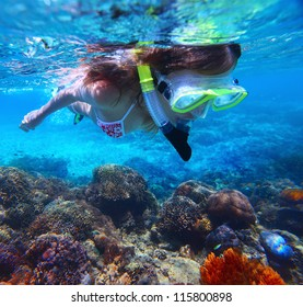 Young woman snorkeling over vivid coral reef in tropical sea