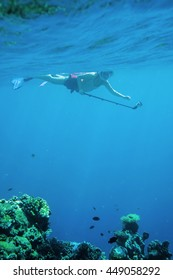 young woman snorkeling with selfie stick and action camera vertical above coral ground