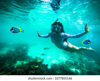 Young woman at snorkeling in the tropical Oliveli island , Maldives.